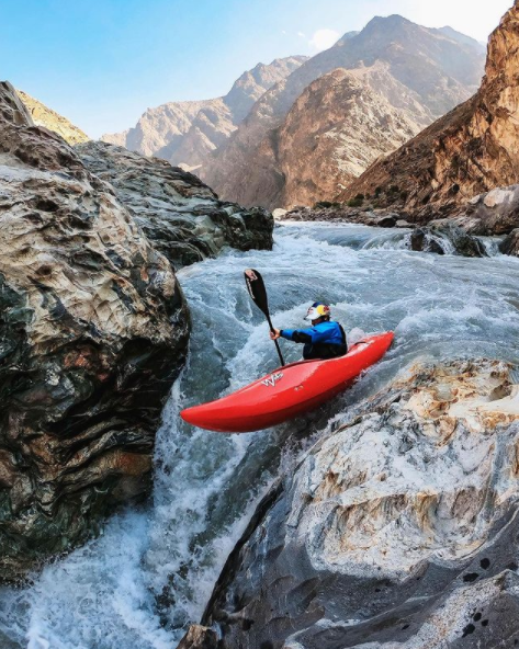 In this picture taken off Go Pro's Instagram account there is a person in a blue jacket in a red kayak going down some rapids. In the background of the image there are mountains and a blue sky. Building an online presence.