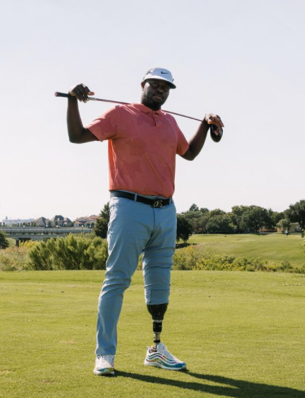 This image shows golfer Carlos Brown stood with a golf club over his shoulders and both hands resting on it. He is wearing a white cap white a black Nike tick, a coral polo shirt, light blue trousers with a black belt, and white and blue striped AirMax 97s. On his left leg the trousers are rolled up to the knee, revealing his black prosthetic leg. He is stood on a golf course, in the background of the image there is green grass and a clear sky.