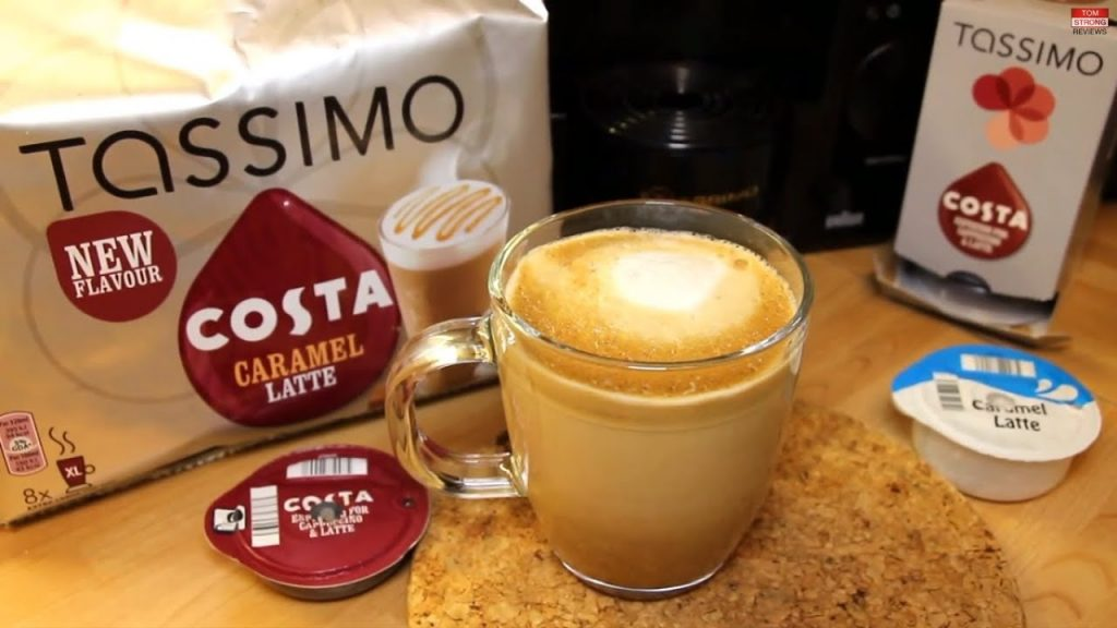 Image shows a light wooden kitchen surface. On it there is a packet of Costa caramel latte Tassimo podss. The coffee and milk pods used are displayed next to a glass mug filled with coffee.